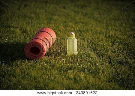 Sport Equipment. Mat And Plastic Bottle On Green Grass, Gym Equipment. Thirst, Dehydration, Drinking