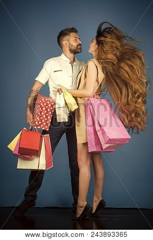 Fashion Shopaholic Couple. Shopping And Sale. Couple In Love Hold Shopping Bag Near Blue Wall.