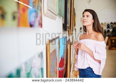 Woman Looking At Paintings In Art Gallery
