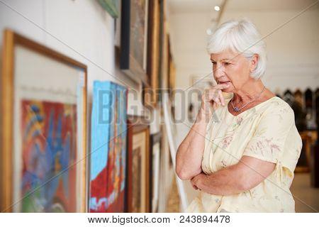 Senior Woman Looking At Paintings In Art Gallery