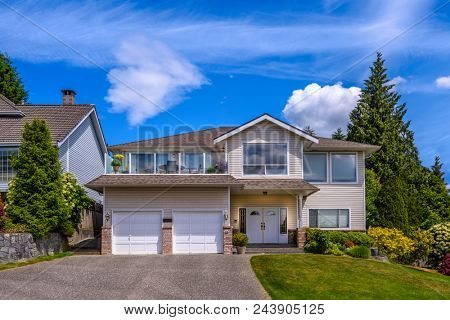 A perfect neighborhood Houses in suburb at Summer in the north America. Fragment of a luxury house with nice window over blue sky.