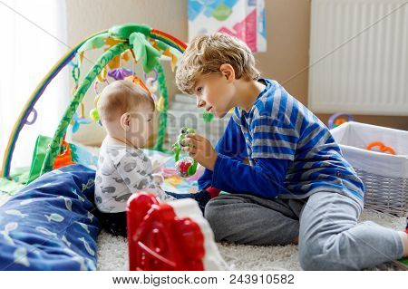 Happy Little Kid Boy With Newborn Baby Girl, Cute Sister. Siblings. Brother And Baby Playing Togethe