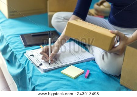 Business Owner Writes And Check Packing List Order On Bedroom. Pack Boxes, Shipping Parcel Package A