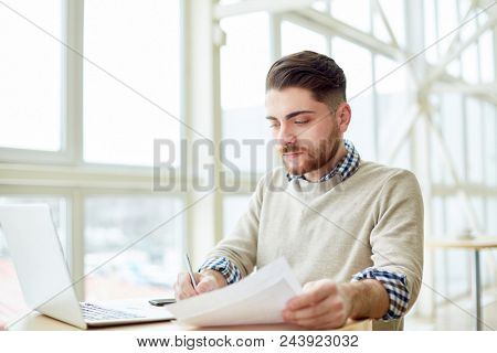 Young man working with papers and watching laptop while writing at table in light room