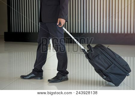 Businessman Drag Luggage Or Suitcase Walking To The Hotel Lobby.