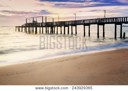 The Old Bridge Into The Sea On The Beach With Sunset Sky Background.