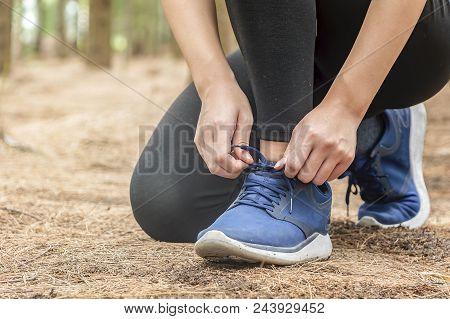 Young Woman Runner Tying Shoelaces In Forest