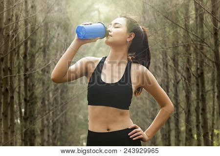 Young Asian Woman Drinking Water During Morning Jogging.girl Quenches Thirst After Fitness Outdoors.