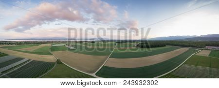 Amazing aerial panorama image of green agricultural fields with clouds during dusk