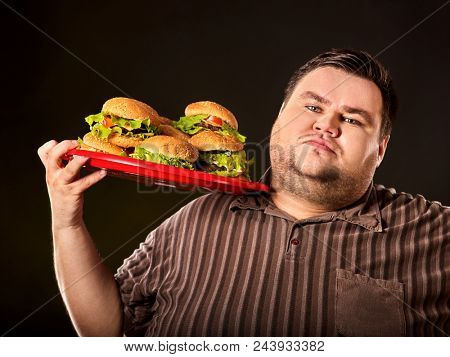 Fat man eating fast food hamberger and carries treat for friends on tray. Breakfast for overweight person. Junk meal leads to obesity. Expensive fast food restaurant. Fatso with tray of harmful food.
