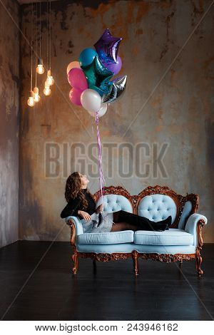Charming Young Brunette Woman Holding A Large Bundle Of Helium Balloons Lying On Sofa In Minimalisti