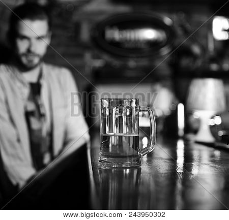 Glass Of Beer. Glass Of Draft Beer On Blurred Bar Background. Man Sits In Pub Near Glass Of Beer On