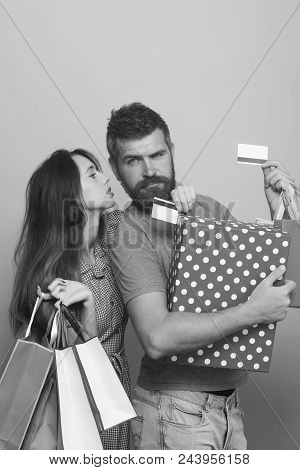 Couple In Love Hugs Holding Big Box And Shopping Bags On Pink Background. Guy With Beard And Pretty