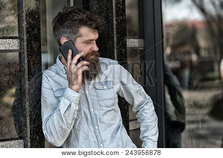 Man With Beard And Mustache On Strict Face Talking, Building On Background. Bearded Man Speaking On