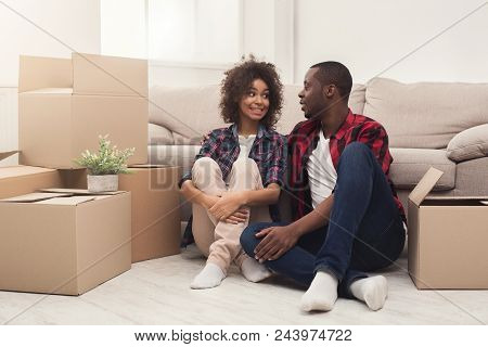 Happy African-american Couple Having Rest While Unpacking Moving Boxes In New Apartment, Copy Space