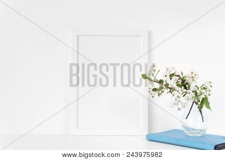White Frame Mock Up With Spring Cherry Bouquet And Blue Notebook. Mock Up For Your Photo, Design Or