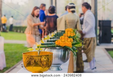 To make merit by offering food to monk ceremony in Thai wedding tradition.Selective focus on Flower bouquet. poster