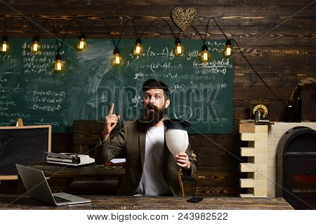 Scientist Hipster With Lightbulb On Chalkboard. Bearded Man Hold Bulb In Classroom. Businessman In S