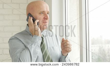 Pleased Businessperson Image Talking To Cell Phone In Office Room