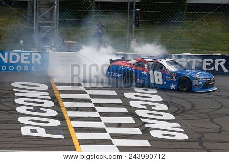 June 02, 2018 - Long Pond, Pennsylvania, USA: Kyle Busch (18) does a burnout after winning the Pocono Green 250 at Pocono Raceway in Long Pond, Pennsylvania.