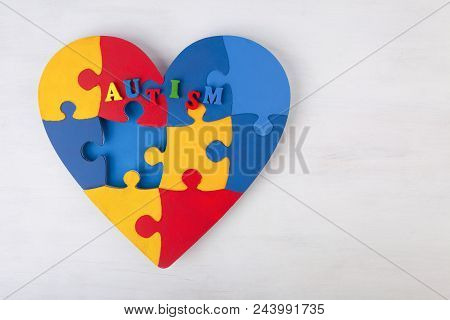 A Colorful Heart Made Of Symbolic Autism Puzzle Pieces On White Wooden Background