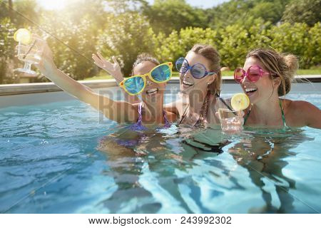 Girl friends in swimming-pool, bachelor party