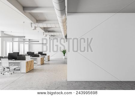 Open Space Office Interior With White Walls, A Concrete Floor And Rows Of Computer Tables. A Blank W