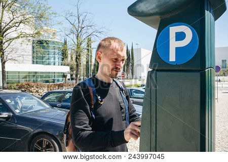 A Man Pays For Parking Using A Special Machine To Pay In Lisbon In Portugal.