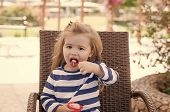 Happy kid having fun. Food, refreshing dessert eating concept. Boy with icecream in outdoor cafe. Kid with frozen fruit yogurt, gelato or sorbet. Child eat ice cream in cup with spoon. poster