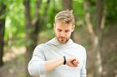 Sportsman training with pedometer gadget. Man athlete on busy face check fitness tracker, nature background. Athlete with bristle with fitness tracker or pedometer. Sport gadget concept. poster