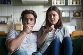 Scared millennial couple watching horror movie on tv holding remote control at home, frightened young man and woman feeling fear or surprise during thrilling scary film moment sitting on sofa at home poster