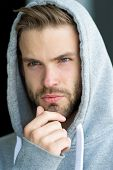 Guy bearded and attractive touches bristle on chin. Masculinity concept. Man with beard or unshaven guy looks handsome hooded. Man with bristle on serious face, urban background, defocused. poster