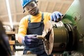 Confident African American machine operator wearing safety goggles and hardhat adjusting equipment while working at production department of modern plant poster