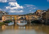 Ponte Vecchio (Old Bridge) in Florence, Tuscany, Italy. This medieval stone bridge, that spans river Arno,  consists of three segmental arches and it has always hosted shops and merchants. poster