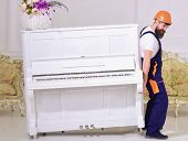 Loader moves piano instrument. Courier delivers furniture in case of move out, relocation. Man with beard, worker in overalls and helmet lifts up piano, white background. Delivery service concept. poster