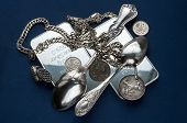 A handful of silver bullion, silverware, jewelery and old silver coins on a dark blue background. poster