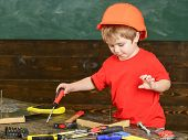 Kid boy holds screwdriver tool. Handcrafting and workshop concept. Child in helmet cute playing as builder or repairer, or handcrafting. Toddler on busy face plays with screwdriver at workshop. poster