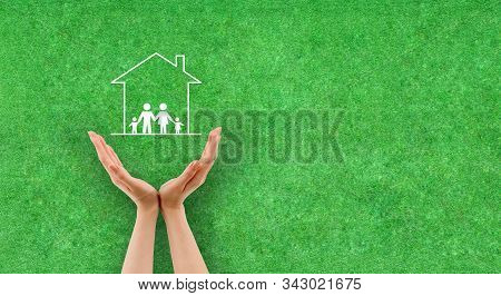 Family Life Insurance Concept : Female Hand Protecting Family And Housing Icons With Green Grass In