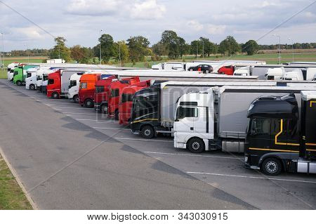 Resting Place. Various Types Of Trucks In A Crowded Parking Lot Off The Highway.