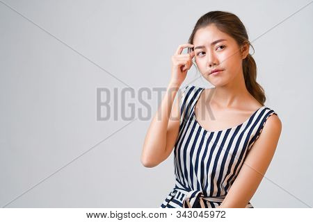 Portrait Of Young Charming Asian Woman Looks Pensive And Curious Thinking Up And Look Sideways At Gr