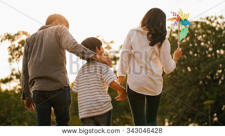 Silhouette Of Back View Of Asian Happy Family Spend Time Together Walking And Relaxing At The Park I