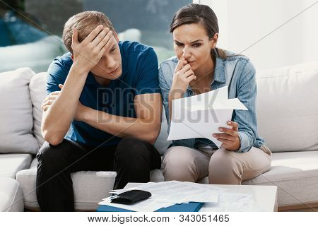 Newly Married Couple Sitting At Home Looking At Their Finance Problems