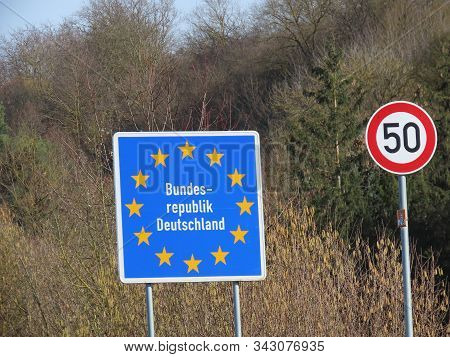 German Border On Small Road. Blue Board With Yellow Eu Stars, Bundesrepublik Deutschland Means Germa