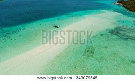 Island With A Sandy Beach And Azure Water Surrounded By A Coral Reef And An Atoll, Aerial View. Mans
