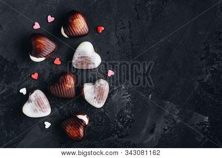 Valentine's Day Chocolate Hearts On The Dark Background. Dark, Milk And White Chocolate Hearts For V