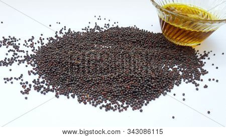 Mustered Seed And Oil In Bowl Isolated On White Background