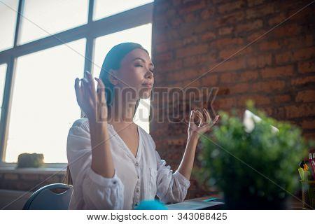 Beautiful Calm Young Woman Meditating At Work