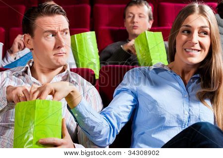 Couple in cinema theater watching a movie, they eating popcorn