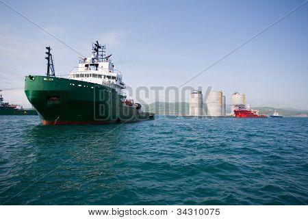 Ocean tugs towing base offshore oil drilling platform. Sea of Japan. Russian coast.