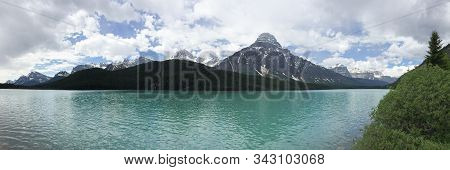Panorama Of A Snow-capped Mountain Rising Above A Turquoise Glacial Lake In Banff, Canada